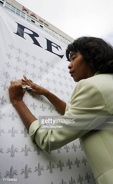 JoAnn Veal signs a wall of Fleur de Lis in remembrance of her mother who died during Hurricane Katrina during the Ringing of the Bells ceremony at...