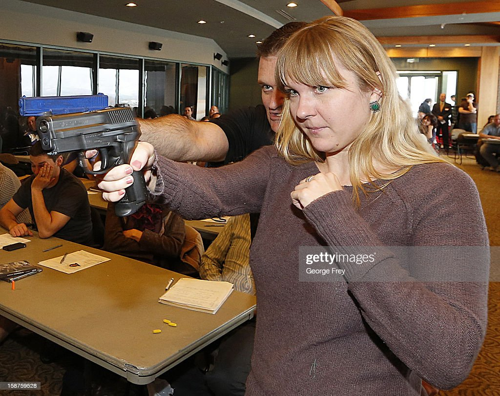 Joanna Baginska (R), a fourth grade teacher at Odyssey Charter School in American Fork, Utah is shown how to handle a 40 cal. Sig Sauer by firearm instructor Clark Aposhian at a concealed-weapons training class to 200 Utah teachers on December 27, 2012 in West Valley City, Utah. The Utah Shooting Sports Council said it would waive its $50 fee for concealed-weapons training for Utah teachers.