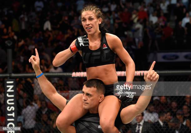 Joanna Jedrzejczyk raises her hands after facing Jessica Andrade in their UFC women's strawweight championship fight during the UFC 211 event at the...
