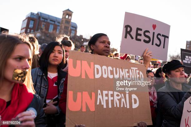 JoAnne Bellamy from Virginia Beach Virginia holds up a sign supporting immigrants during a rally to mark International Women's Day in Washington...