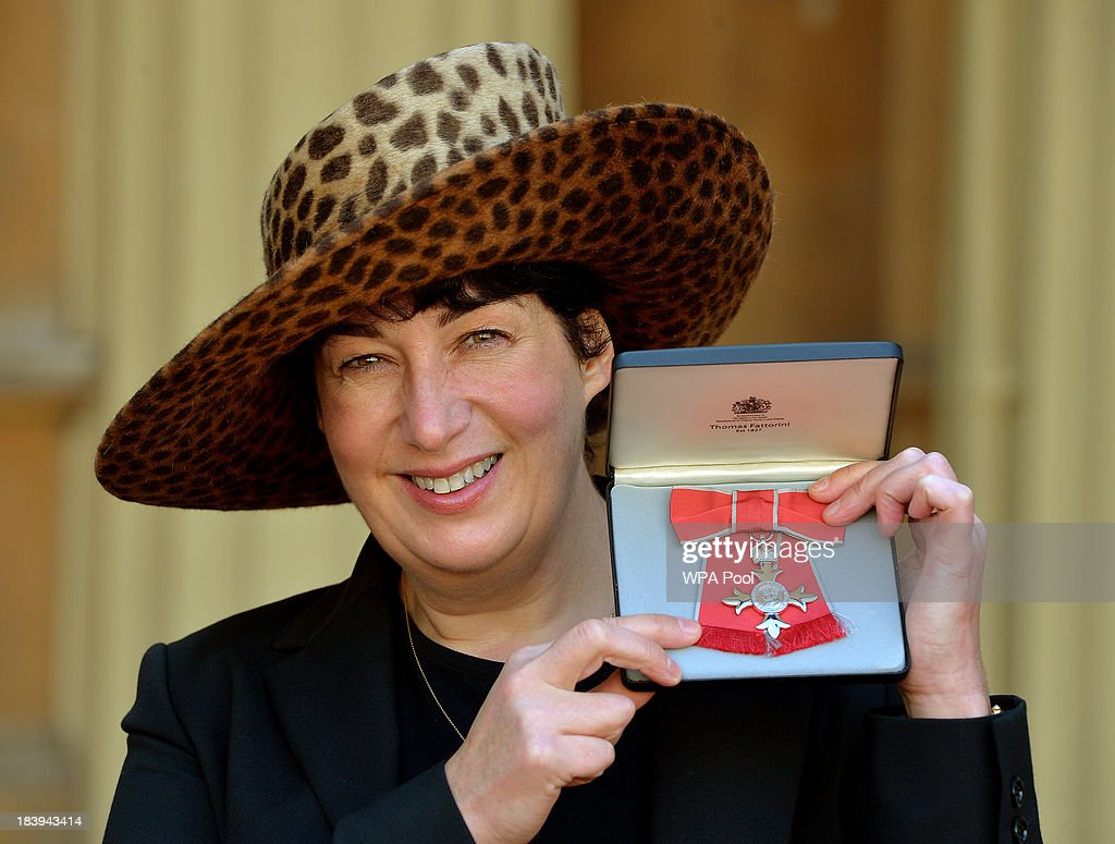 Joanne Harris holding her MBE for services to Literature after it was presented to her by Queen Elizabeth II at an Investiture Ceremony at Buckingham Palace on October 10, 2013 in London, England.
