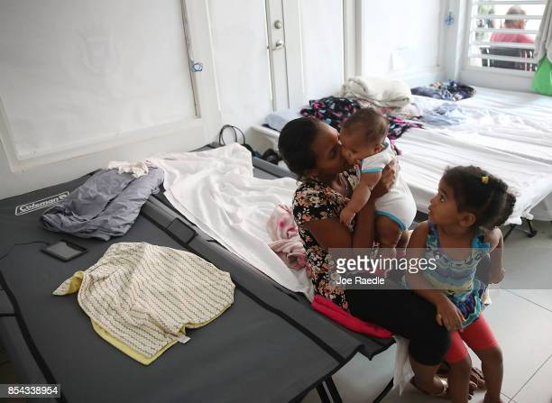 Joanne Torres sits on a cot with her daughters Eliana Heredia and Marianny Reynoso in the Centro de Servicios Integrados de Barrio Obrero shelter...