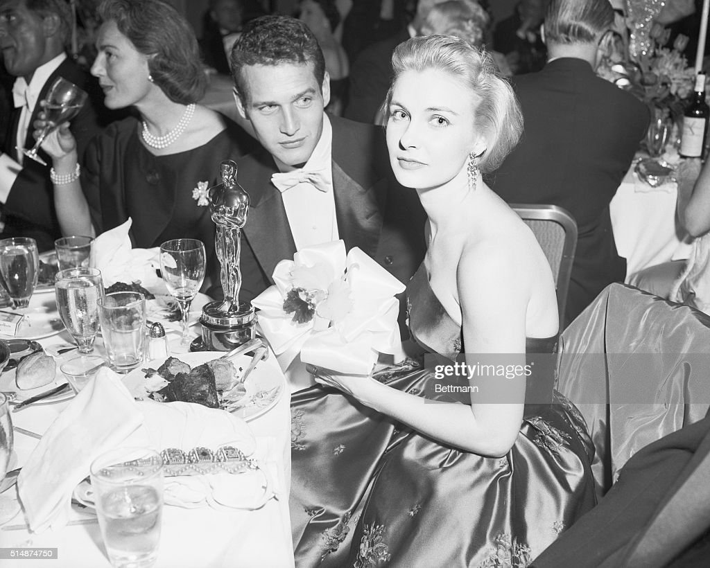 Joanne Woodward, named best actress for her role in The Three Faces of Eve, sits at a dinner table with her husband, Paul Newman, with her Oscar statuette and a congratulatory orchid corsage sent to her by actress Elizabeth Taylor.