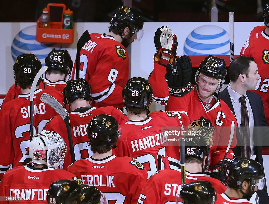 Joanthan Toews #19 of the Chicago Blackhawks (R, facing camera) celebrates with teammates including Michael Handzus #26 after a win against the Detroit Red Wings in Game Seven of the Western Conference Semifinals during the 2013 NHL Stanley Cup Playoffs at the United Center on May 29, 2013 in Chicago, Illinois. The Blackhawks defeated the Red Wings 2-1 in overtime.