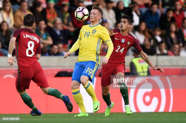 Joao Cancelo of Portugal competes for the ball with Sam Larsson of Sweden during the International friendly match between Portugal and Sweden at...