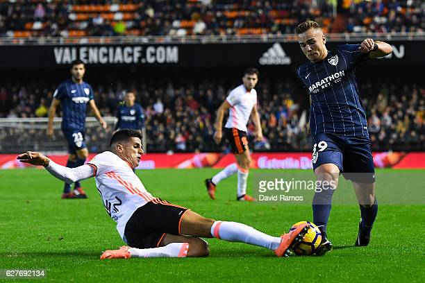 Joao Cancelo of Valencia CF competes for the ball with Javier Ontiveros of Malaga CF during the La Liga match between Valencia CF and Malaga CF at...