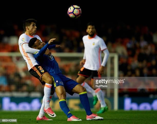 Joao Cancelo of Valencia CF competes for the ball with Theo Bongoxda of Real Club Celta de Vigo during the La Liga match between Valencia CF and Real...