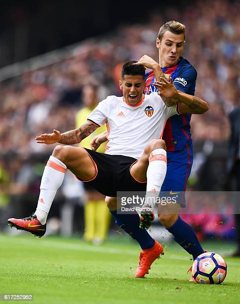 Joao Cancelo of Valencia CF is brought down by Lucas Digne of FC Barcelona during the La Liga match between Valencia CF and FC Barcelona at Mestalla...