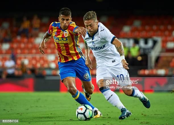 Joao Cancelo of Valencia competes for the ball with Alejandro Gomez of Atalanta during the preseason friendly match between Valencia CF and Atalanta...
