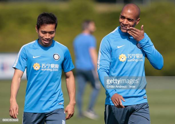 Joao Mario of FC Internazionale Milano smiles with his teammate Yuto Nagatomo during the FC Internazionale training session at the club's training...