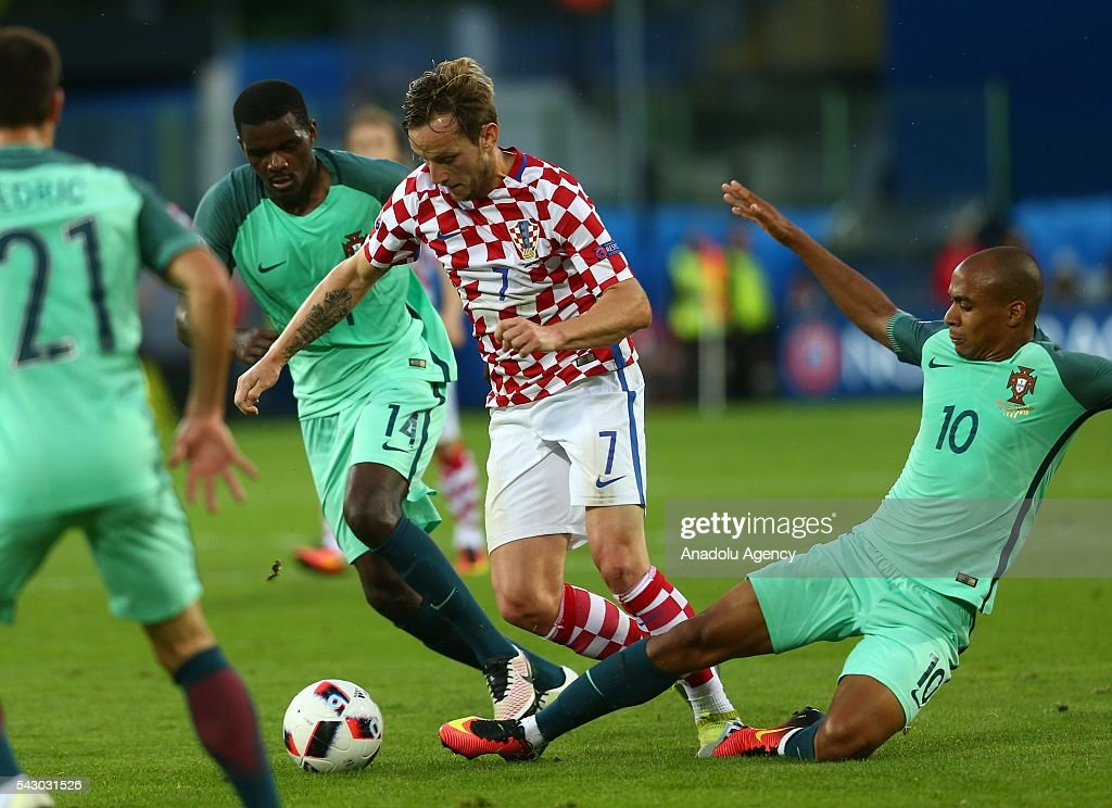 Joao Mario (R) of Portugal in action against Ivan Rakitic (C) of Croatia during the Euro 2016 round of 16 football match between Croatia and Portugal at Stade Bollaert-Delelis in Lens, France on June 25, 2016.