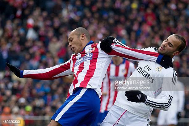 Joao Miranda of Atletico de Madrid and Jese Rodriguez of Real Madrid CF hang themselves during the La Liga match between Club Atletico de Madrid and...