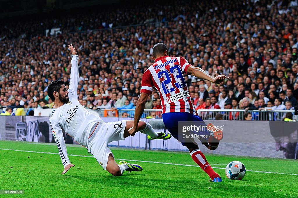 Joao Miranda of Atletico de Madrid clear the ball under pressure from Francisco Alarcon Isco of Real Madrid CF during the La Liga match between Real Madrid CF and Club Atletico de Madrid at Bernabeu on September 28, 2013 in Madrid, Spain.