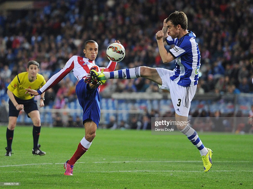 Joao Miranda of Club Atletico de Madrid battles for the ball Mikel Gonzalez of Real Sociedad during the La Liga match between Club Atletico de Madrid...