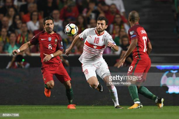 Joao Moutinho of Portugal competes for the ball with Admir Mehmedi of Switzerland during the FIFA 2018 World Cup Qualifier between Portugal and...