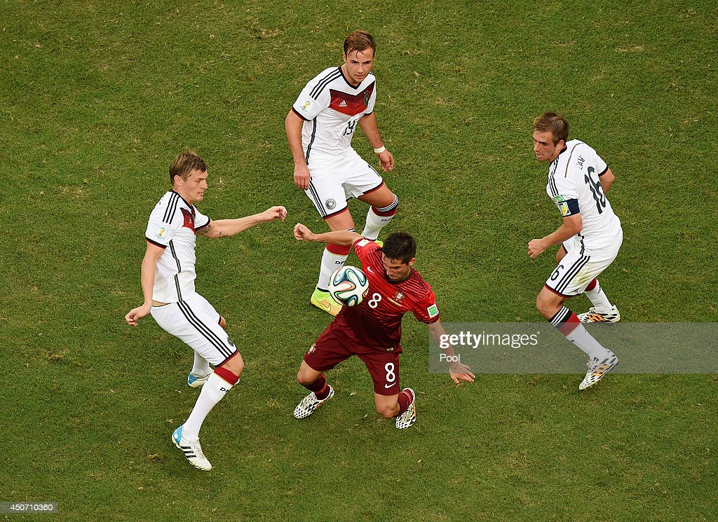 Joao Moutinho of Portugal takes on Toni Kroos of Germany Mario Goetze and Philipp Lahm during the 2014 FIFA World Cup Brazil Group G match between...