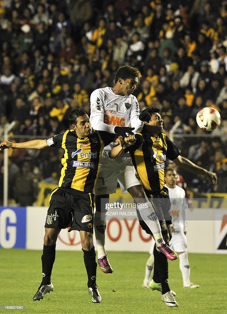 Joao (C) of Brazil's Atletico Mineiro vies for the ball with Marcos Barrera (L) and Luis Mendez of Bolivia's The Strongest during their Copa Libertadores football match at Hernando Siles stadium in La Paz, Bolivia, on March 13, 2013. AFP PHOTO/Aizar Raldes