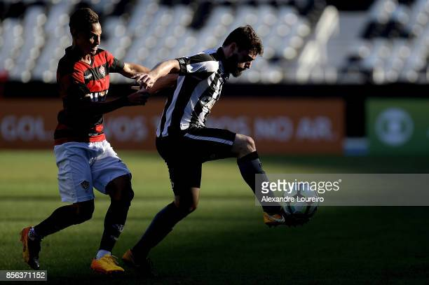 Joao Paulo of Botafogo battles for the ball with Neilton of Vitoria during the match between Botafogo and Vitoria as part of Brasileirao Series A...