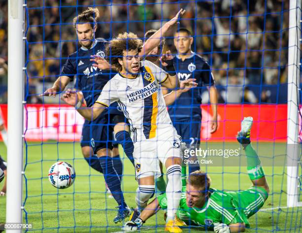 Joao Pedro of Los Angeles Galaxy follows a header by Dave Romney of Los Angeles Galaxy into the net as Tim Melia of Sporting Kansas City tries to...