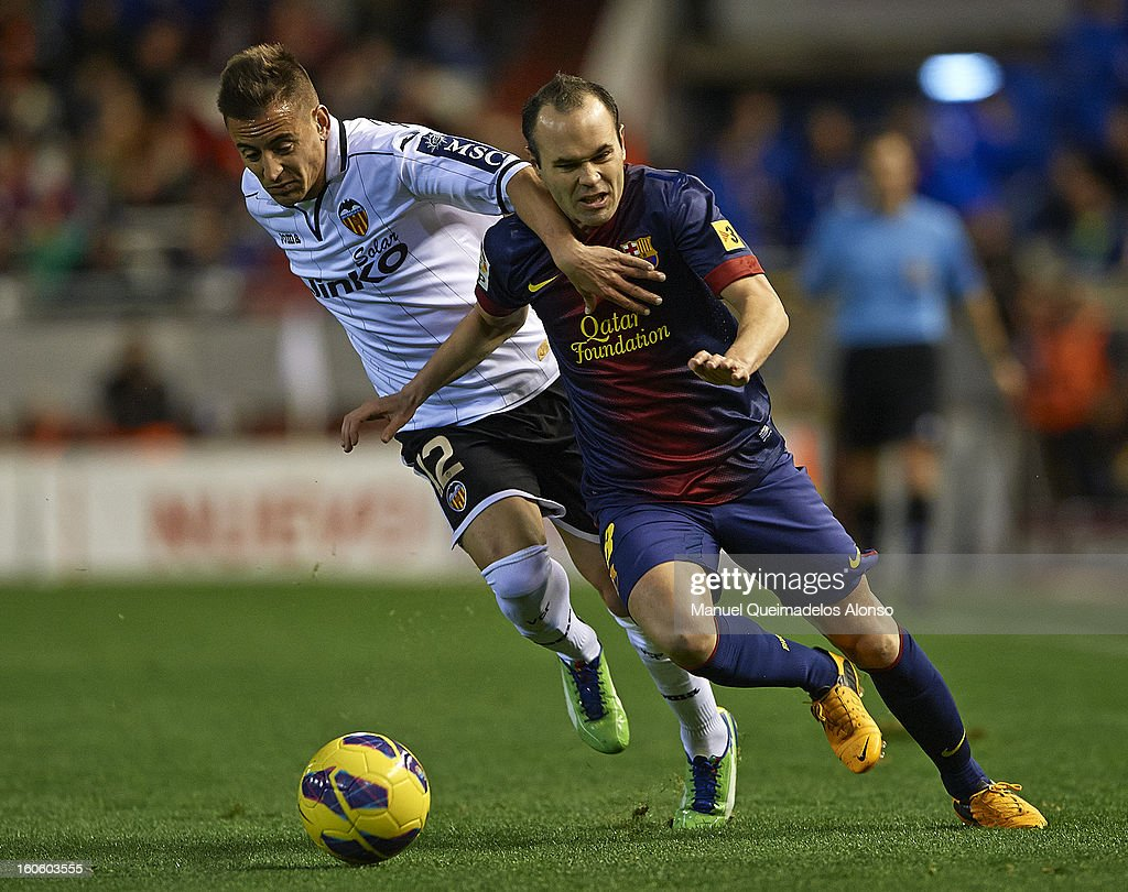 Joao Pereira (L) of Valencia competes for the ball with Andres Iniesta of Barcelona during the La Liga match between Valencia and Barcelona Estadio Mestalla on February 3, 2013 in Valencia, Spain.