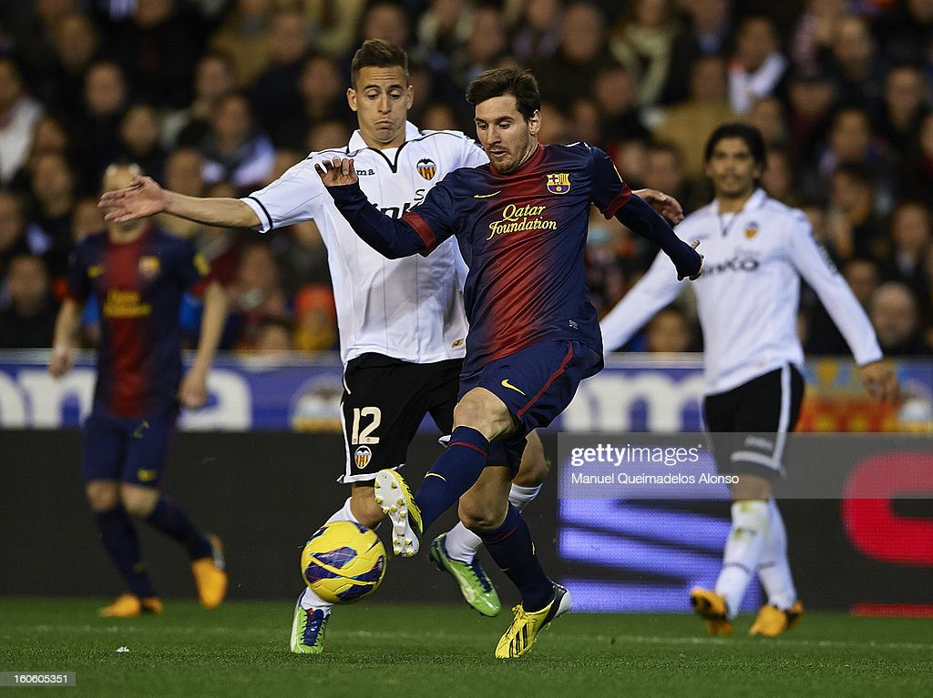 Joao Pereira (L) of Valencia competes for the ball with <a gi-track='captionPersonalityLinkClicked' href=/galleries/search?phrase=Lionel+Messi&family=editorial&specificpeople=453305 ng-click='$event.stopPropagation()'>Lionel Messi</a> of Barcelona during the La Liga match between Valencia and Barcelona Estadio Mestalla on February 3, 2013 in Valencia, Spain.