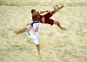 Joao Saraiva of Portugal is challenged by Ilia Leonov of Russia during the Men's Beach Soccer semi final match between Portugal and Russia during day...