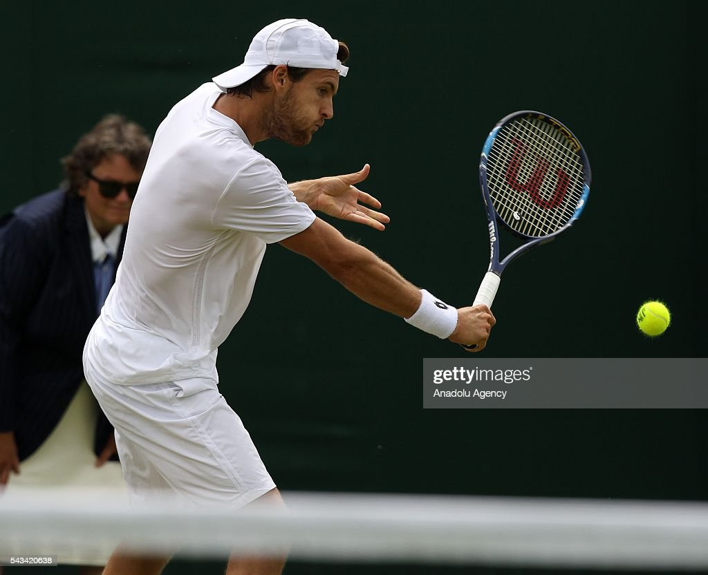 Joao Sousa of Portugal (C) in action against Dmitry Tursunov (not seen) of Russia during the Men's Singles match on day two of the 2016 Wimbledon Championships at the All England Lawn and Croquet Club in London, United Kingdom on June 28 2016.