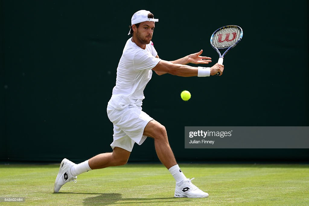 Joao Sousa of Portugal plays a backhand during the Men's Singles first round match against Dmitry Tursunov of Russia on day two of the Wimbledon Lawn Tennis Championships at the All England Lawn Tennis and Croquet Club on June 28, 2016 in London, England.