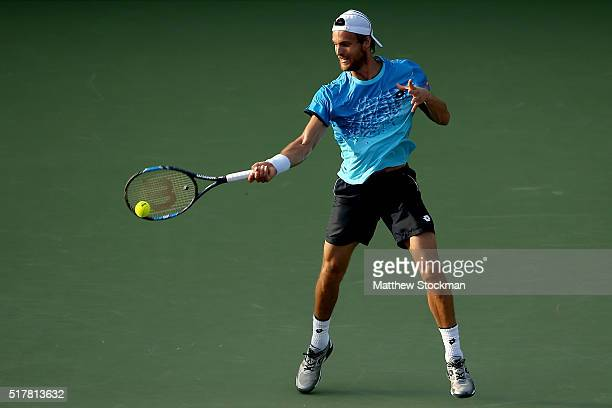 Joao Sousa of Portugal returns a shot to Novak Djokovic of Serbia during the Miami Open presented by Itau at Crandon Park Tennis Center on March 27...