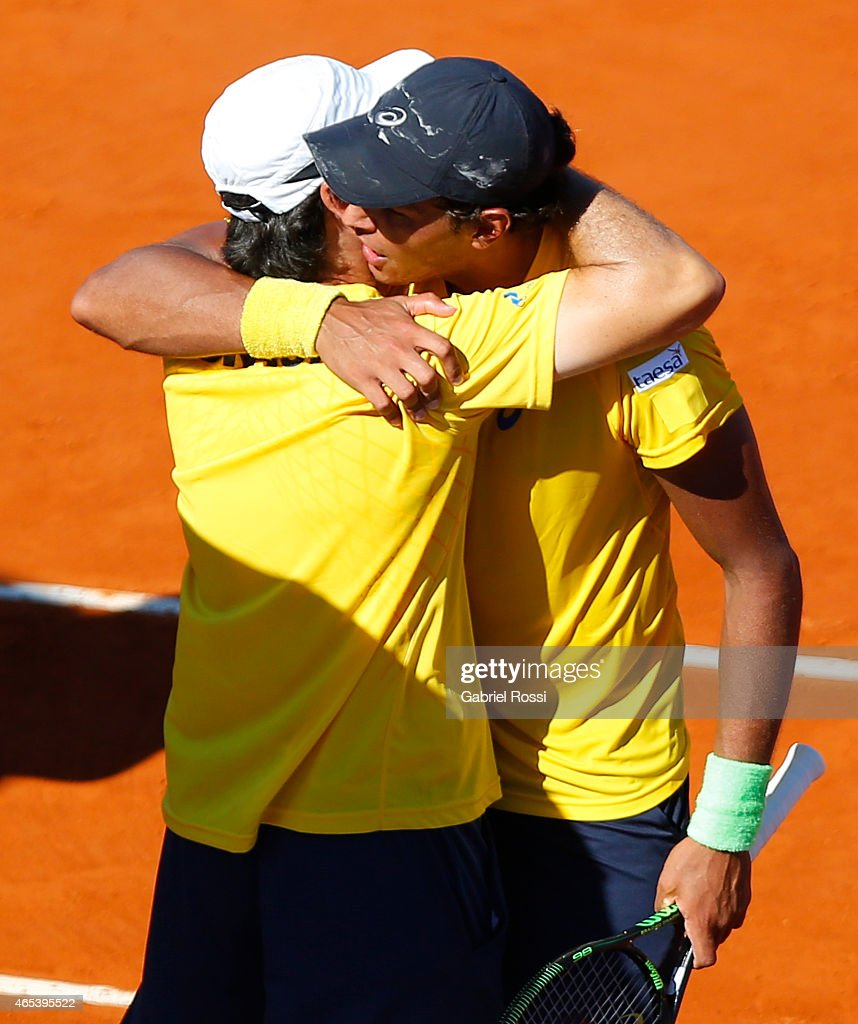 Joa‹o Souza of Brazil celebrates with Joao Zwetsch coach of Brazil after wining the singles match between <a gi-track='captionPersonalityLinkClicked' href=/galleries/search?phrase=Carlos+Berlocq&family=editorial&specificpeople=553854 ng-click='$event.stopPropagation()'>Carlos Berlocq</a> of Argentina and Jo‹ao Souza of Brazil as part of Davis Cup 2015 match between Argentina and Brazil at Tecnopolis on March 06, 2015 in Villa Martelli, Buenos Aires, Argentina.