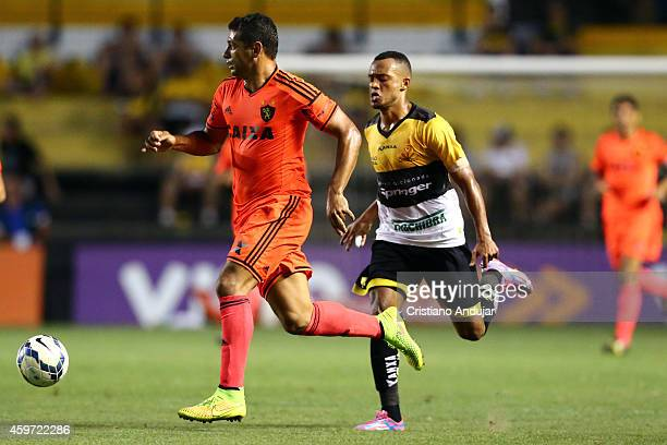 Joao Vitor of Criciuma try to stop Diego Souza of Sport during a match between Criciuma and Sport as part of Campeonato Brasileiro 2014 at Heriberto...