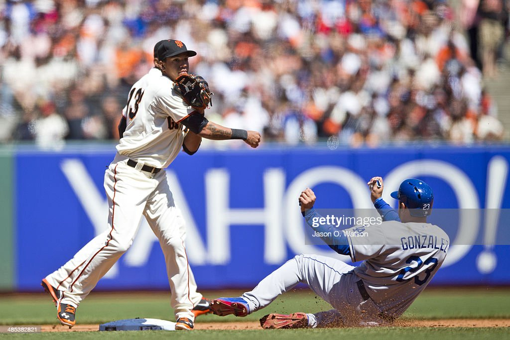 Joaquin Arias #13 of the San Francisco Giants completes a double play over Adrian Gonzalez #23 of the Los Angeles Dodgers during the fifth inning at AT&T Park on April 17, 2014 in San Francisco, California.
