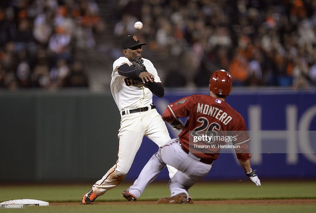 Joaquin Arias of the San Francisco Giants gets his throw over the top of Miguel Montero of the Arizona Diamondbacks but not in time to complete the...