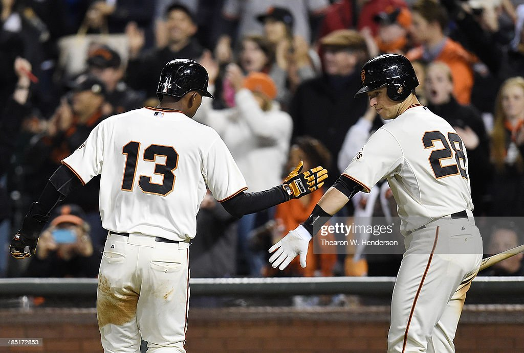 Joaquin Arias #13 of the San Francisco Giants is congratulated by <a gi-track='captionPersonalityLinkClicked' href=/galleries/search?phrase=Buster+Posey&family=editorial&specificpeople=4896435 ng-click='$event.stopPropagation()'>Buster Posey</a> #28 after Arias scored in the bottom of the seventh inning against the Los Angeles Dodgers at AT&T Park on April 16, 2014 in San Francisco, California. Arias scored on an RBI single from Pablo Sandoval.