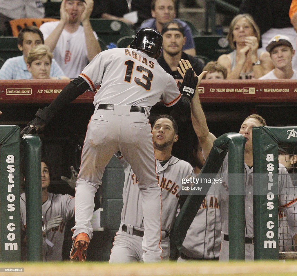 Joaquin Arias #13 of the San Francisco Giants receives a high five from <a gi-track='captionPersonalityLinkClicked' href=/galleries/search?phrase=Hunter+Pence&family=editorial&specificpeople=757341 ng-click='$event.stopPropagation()'>Hunter Pence</a> #8 of the San Francisco Giants after scoring in the ninth inning against the Houston Astros at Minute Maid Park on August 28, 2012 in Houston, Texas.