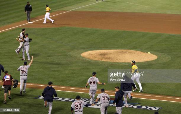 Joaquin Benoit and Alex Avila of the Detroit Tigers is congratulated by teammates including Justin Verlander after they beat the Oakland Athletics in...