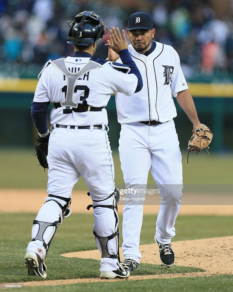 Joaquin Benoit #53 of the Detroit Tigers hi-fives teammate Alex Avila #13 after defeating the New York Yankees 8-4 at Comerica Park on April 6, 2013 in Detroit, Michigan.