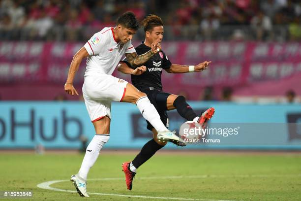 Joaquin Correa of Sevilla FC and Riku Matsuda of Cerezo Osaka compete for the ball during the preseason friendly match between Cerezo Osaka and...