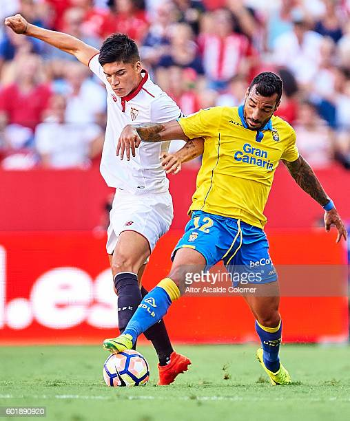 Joaquin Correa of Sevilla FC competes for the ball with Javi Castellano of Union Deportiva Las Palmas during the match between Sevilla FC vs UD Las...