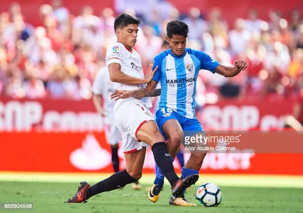 Joaquin Correa of Sevilla FC competes for the ball with Roberto Rosales of Malaga CF during the La Liga match between Sevilla and Malaga at Estadio...