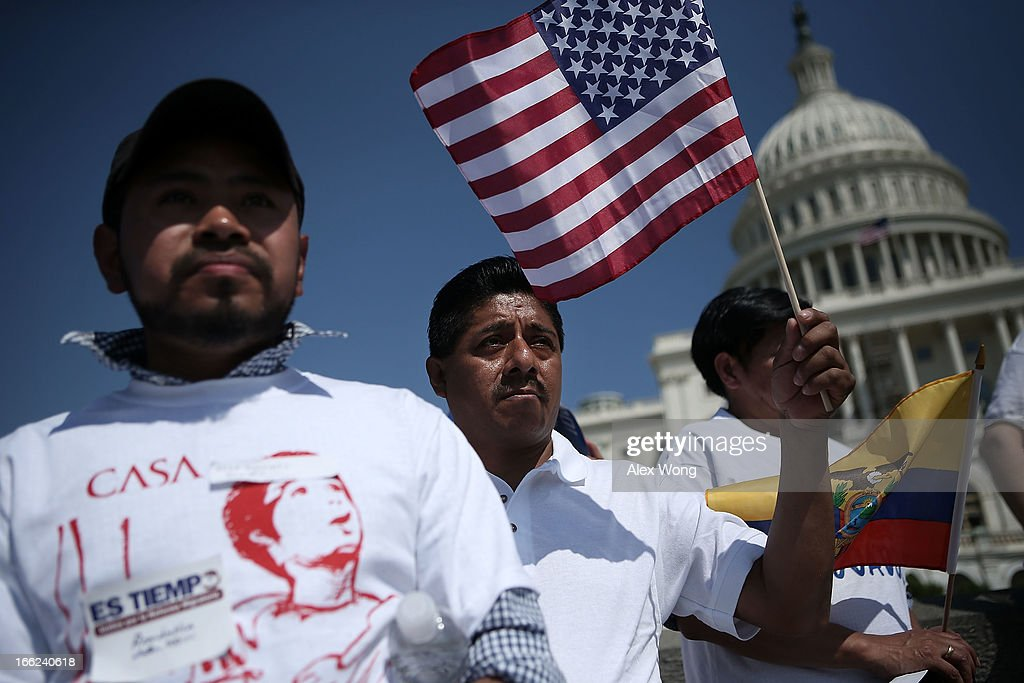 Joaquin Diaz (C) of Langley Park, Maryland, holds up a U.S. flag as he gathers with other immigration activists on the West Lawn of the U.S. Capitol for an All In for Citizenship rally April 10, 2013 on Capitol Hill in Washington, DC. Tens of thousands of reform supporters gathered for the rally to call on Congress to act on proposals that would grant a path to citizenship for an estimated 11 million of the nation's illegal immigrants.