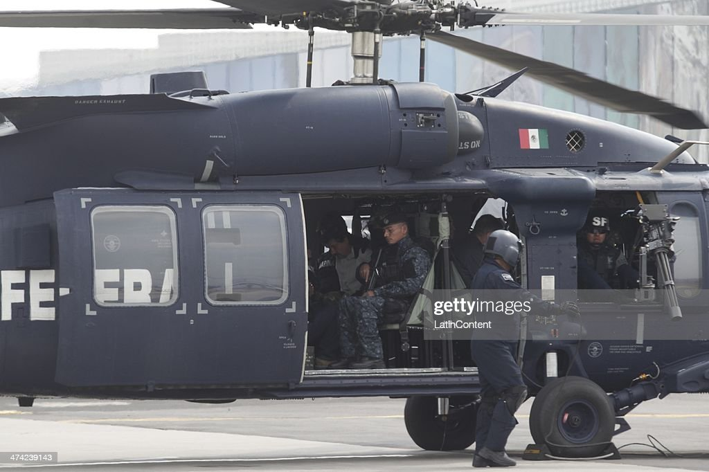 Joaquin 'El Chapo' Guzman is escorted in a helicopter in handcuffs by Mexican navy marines at a navy hanger. Guzman leader of Mexico's Sinaloa drug Cartel, was captured alive overnight in the beach resort town of Mazatlan, considered the Mexican most-wanted drug dealer on February 22, 2014 in Mexico City, Mexico.