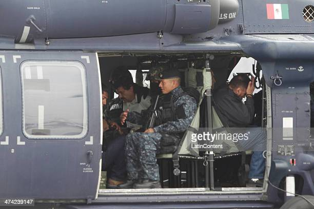 Joaquin 'El Chapo' Guzman is escorted in a helicopter in handcuffs by Mexican navy marines at a navy hanger Guzman leader of Mexico's Sinaloa drug...