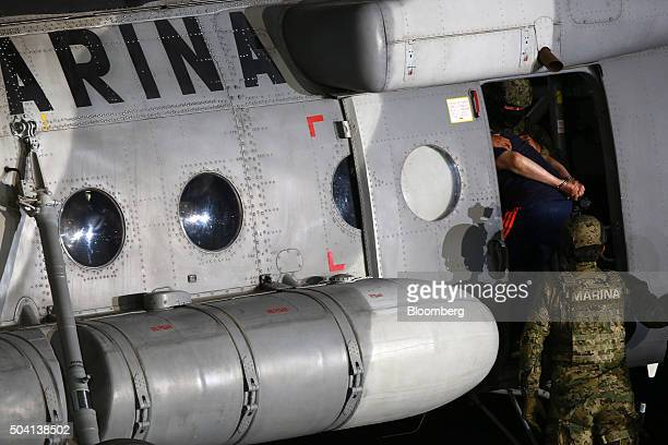 Joaquin Guzman the world's most wanteddrug trafficker is escorted by Mexican security forces into a helicopter at a Navy hangar in Mexico City Mexico...