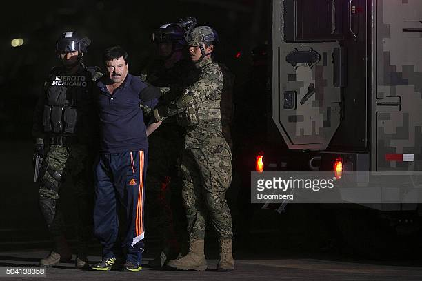 Joaquin Guzman the world's most wanteddrug trafficker second left is escorted by Mexican security forces at a Navy hangar in Mexico City Mexico on...