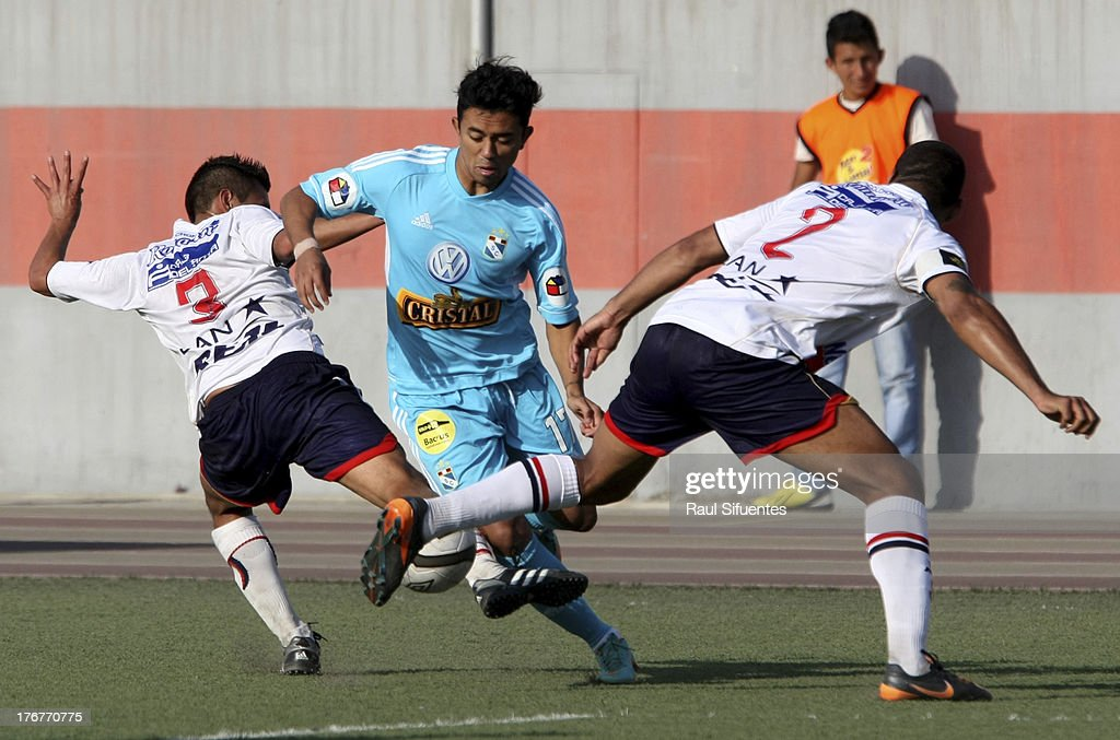 Joazinho Arroe (C) of Sporting Cristal fights for the ball with Manuel Tejada (L) and Giancarlo Carmona (R) of Jose Galvez during a match between Jose Galvez and Sporting Cristal as part of The Torneo Descentralizado 2013 at the Estadio Manuel Rivera Sanchez on August 18, 2013 in Chimbote, Peru.