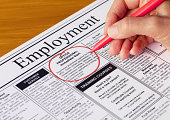 Finding a job in the employment section of the newspaper