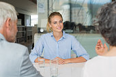 Portrait of beautiful young woman sitting in front of manager and senior leader during a job interview. Senior business people in conversation with a young business woman.  Recruiter checking the cand