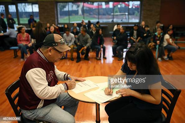 A job seeker fills out paperwork as he is interviewed during a job fair at California's Great America theme park on February 6 2015 in Santa Clara...