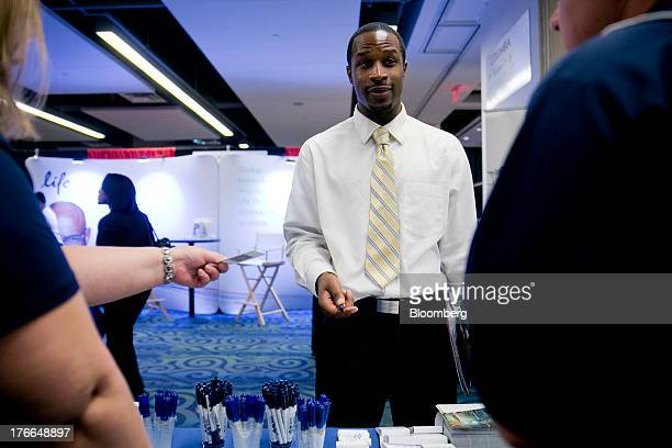 Job seeker Gerald Porter talks to job recruiters at the Black Data Processing Associates career fair in Washington DC US on Friday Aug 16 2013 The US...